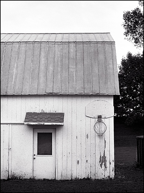 A broken basketball hoop on an old white barn in Fort Wayne, Indiana.