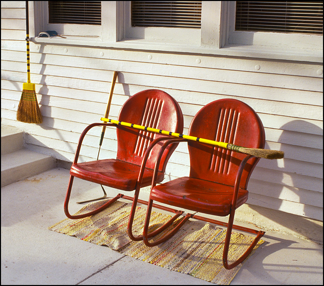 A yellow broom laid across the armrests of two old red metal motel chairs on the back porch of an old white clapboard farm house.