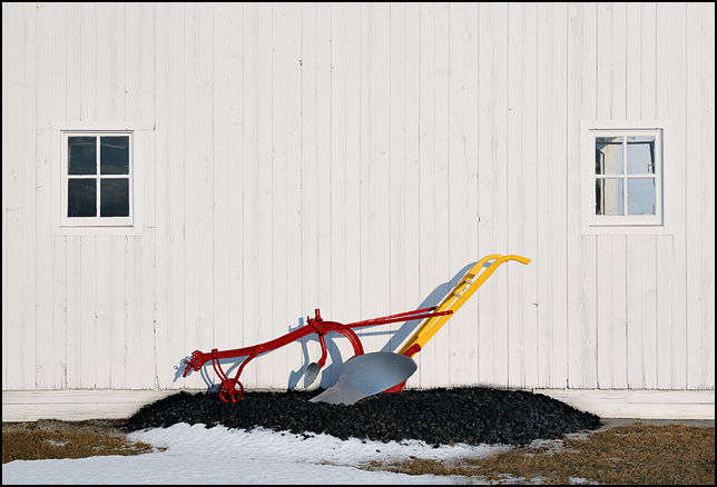 A red and yellow antique horse-drawn plow on display next to a white barn at a farm on State Road 1 in Wells County, Indiana.