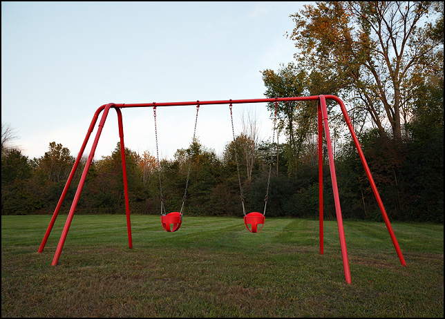 A red swing set in the warm light at the end of the day in late summer.