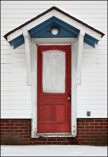 A red door with a boarded up window and fancy molding on the side of an old house in an inner-city neighborhood in Fort Wayne, Indiana.