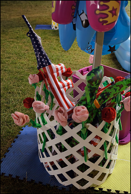 An inflatable M16 assault rifle in the colors of the American flag in a basket of prizes at a carnival.