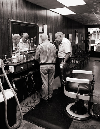 A customer pays small town barber Rex Ottinger for his haircut at Rex's Barbershop in Roanoke, Indiana.