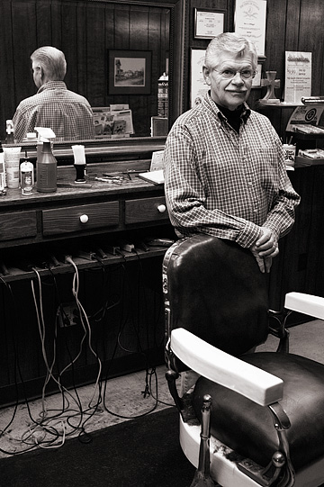 Small town barber Rex Ottinger stands behind one of the historic old Koken barber chairs in his barbershop in Roanoke, Indiana.