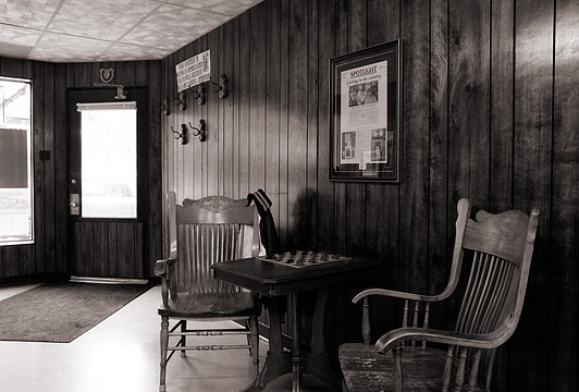 Two old wooden chairs sit beside a table with a checkerboard in the waiting area of Rex Ottinger's small town barbershop in Roanoke, Indiana.