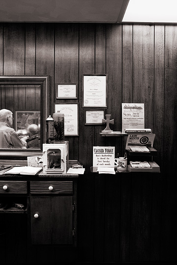 Rex Ottinger's diplomas and boxes of Lions Club Mints on display in the area behind the barber's chair where customers pay for their haircuts in his small town barbershop in Roanoke, Indiana. The barber can be seen reflected in the mirror.