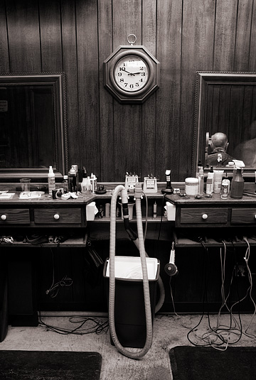 An old clock hangs over a counter covered in clippers and hair care products at Rex's Barbershop in Roanoke, Indiana. A customer's head is reflected on one of the mirrors.