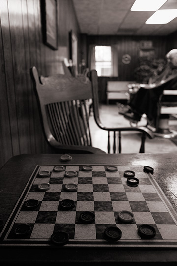 A checkerboard and antique wooden chair in a small town barbershop in Roanoke, Indiana. A customer can be seen in the background getting a haircut from Rex Ottinger.
