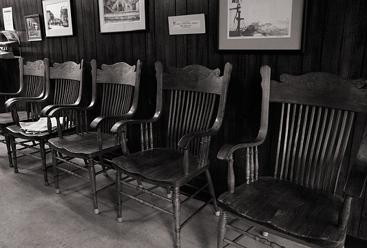 A long row of old wooden chairs sit along the wall in the waiting area in Rex Ottinger's small town barbershop in Roanoke, Indiana. Historic drawings of the town of Roanoke hang above the chairs on the paneled walls.