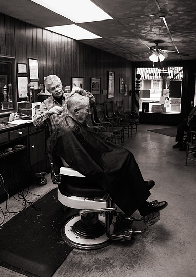 Small town barber Rex Ottinger cuts an elderly gentleman's hair in his barbershop in Roanoke, Indiana. The customer sits in one of the old Koken barber's chairs with enameled armrests and chromed brass fixtures.