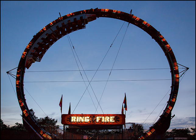 The Ring of Fire carnival ride with its colorful lights in front of a beautiful purple sunset.