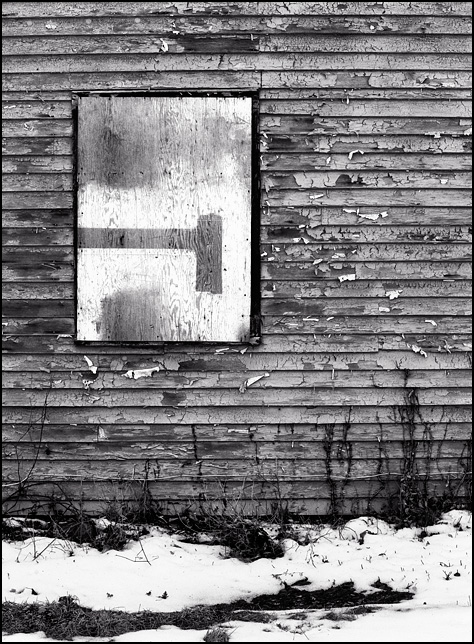A boarded up window on an abandoned house with peeling paint and weathered siding in the Riverhaven neighborhood outside New Haven, Indiana.
