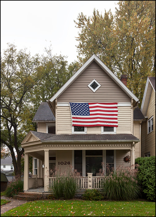 An old victorian style house with a huge American flag covering the entire front of the second story facade, including the windows. Located on Rivermet Avenue in Fort Wayne, Indiana.