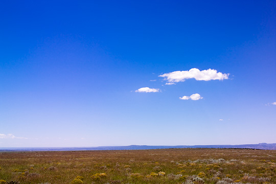 Clouds hang in the deep blue sky over an empty landscape at the edge of La Bajada Mesa in New Mexico.