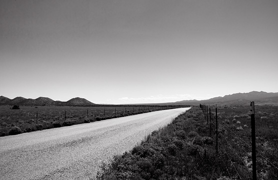 New Mexico landscape with Waldo Canyon Road stretching off into the distance toward the Ortiz Mountains.
