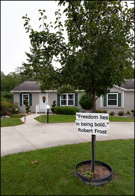A sign with a Robert Frost quote in the front yard of a house in the small town of Saint Joe, Indiana. Freedom Lies In Being Bold.