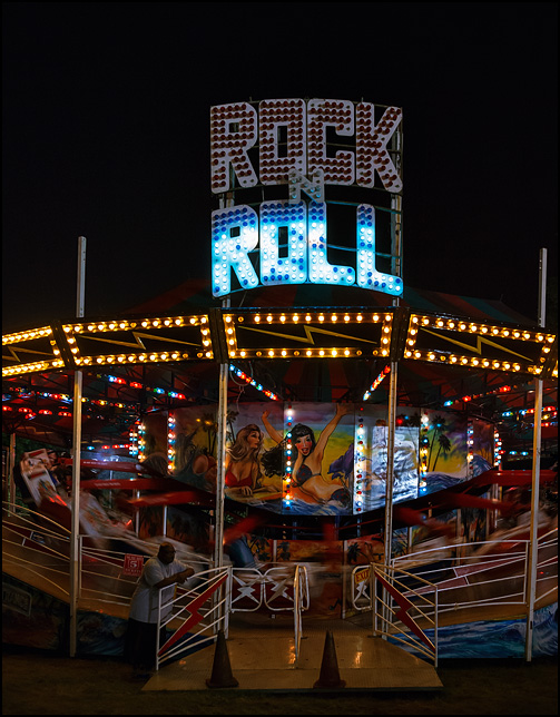 The brightly lit colorful Rock-N-Roll carnival ride in motion at night.