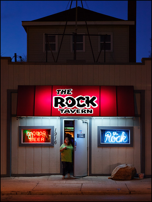 The Rock Tavern on Broadway in Fort Wayne, Indiana. Photographed at night, a woman is walking out the front door smoking a cigarette.