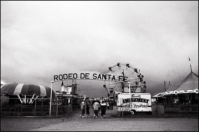A group of teenagers walking through the front gates at the Rodeo de Santa Fe carnival under stormy skies. A ticket booth, ferris wheel, photo booth, and carousel can be seen inside the fence.