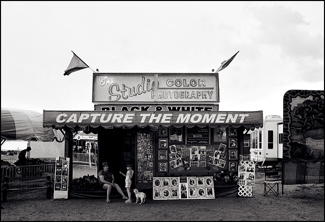 "A little girl and her dog chat with the woman who runs the photo booth at the Rodeo de Santa Fe carnival. The booth has a big sign that says ""Capture the moment"", and the outside is covered in framed portraits."