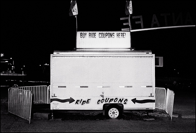 Ticket booth at the Rodeo de Santa Fe carnival after closing time. The trailer is closed up and looks lonely in the dark night.