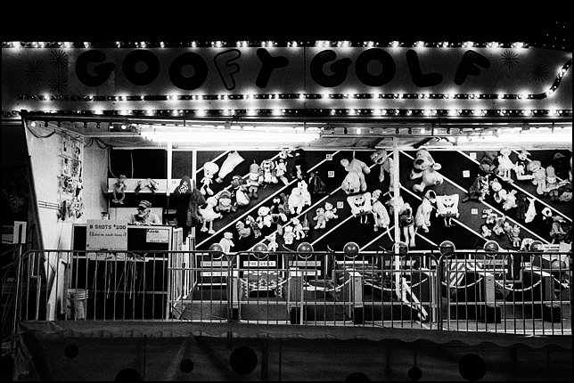 A bored carny waits for someone to play the Goofy Golf game late at night during the Rodeo de Santa Fe carnival.