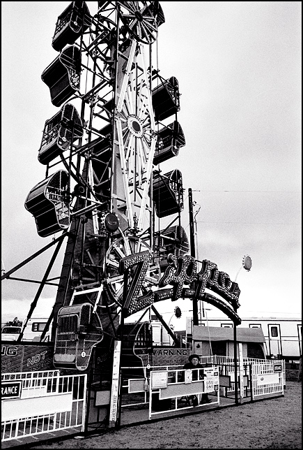 The Zipper Ride at the Rodeo de Santa Fe carnival on a rainy dreary day. The carny looks at me when I take the picture.