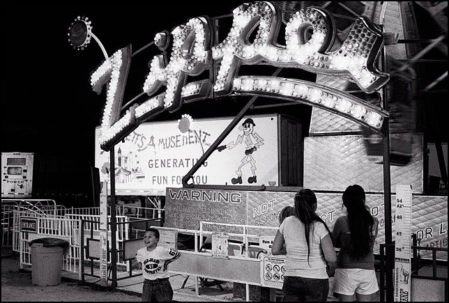 The Zipper Ride at night during the carnival held during the Rodeo de Santa Fe 2007. A little boy jumps with excitement while he waits his turn on the ride.
