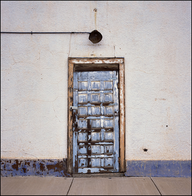 A weathered wood panel door with peeling blue paint on a stucco building in Roswell, New Mexico.