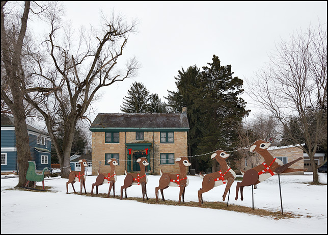A life-size Christmas sleigh and reindeer made from plywood on display in the front yard of a large house on Rudisill Boulevard in Fort Wayne, Indiana.