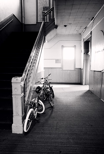 Several childrens bicycles leaning against the stair rail in the main hallway of an old school that has been turned into apartments in Rushville, Indiana.