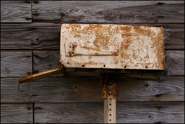 An old rusted mailbox leaned against the weathered wood siding on an abandoned farmhouse on State Road 3 in Huntington County, Indiana.