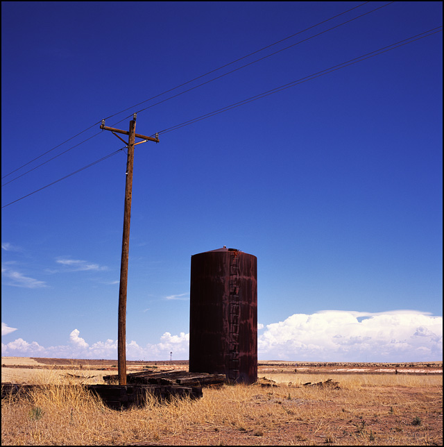 A rusty old water tank and a pile of wooden railroad ties in the New Mexico desert.