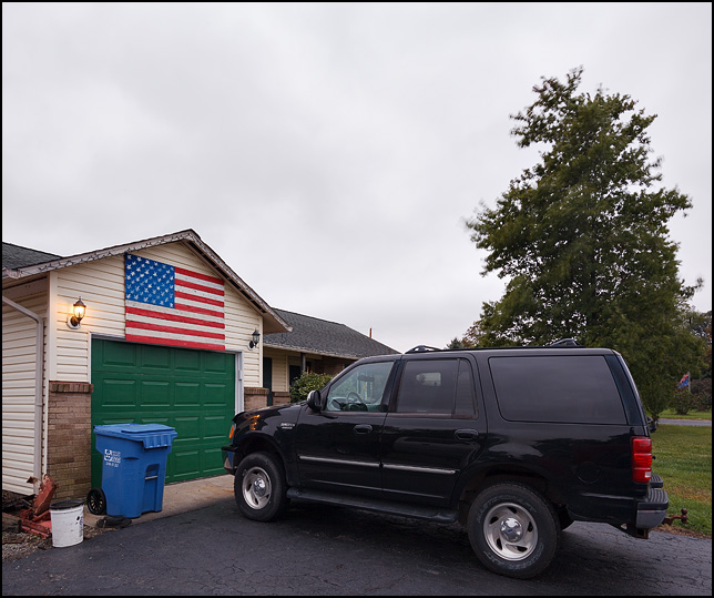 A large handpainted American flag made of wooden fence boards hanging over the garage door of a house on South Circle Drive in Churubusco, Indiana. A black Ford Expedition SUV is parked in front of the garage.