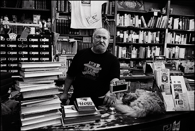Sam Hyde stands behind a pile of books on the counter of his store, Hyde Brothers Books in Fort Wayne, Indiana. A cat sleeps on the counter in front of the cash register.