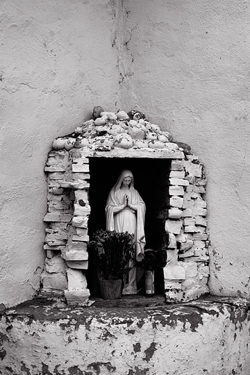 A statue of the Virgin Mary in a stone grotto on the side of the adobe church in the village of San Juan, New Mexico.