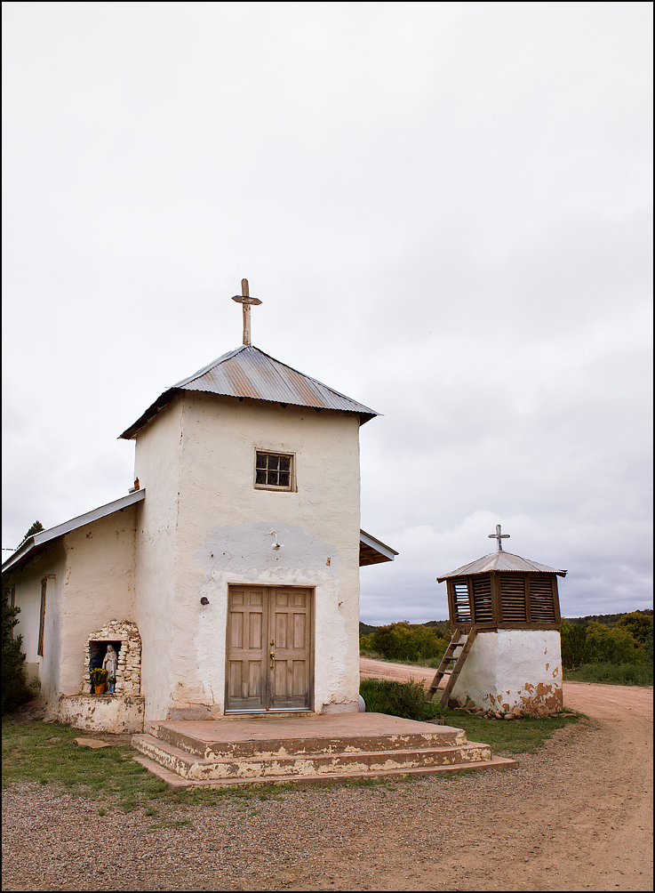 The old adobe Catholic church in the small town of San Juan, New Mexico with separate bell tower next to it and a statue of the Virgin Mary set into a grotto on the outside wall. The church has a tin roof surmounted by a wooden cross and old paneled wood doors. A small ladder allows the sexton to climb into the bell tower.