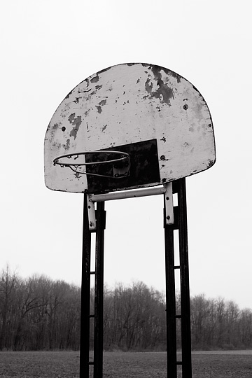 A basketball hoop in front of a field on an abandoned farm in rural Allen County, Indiana.