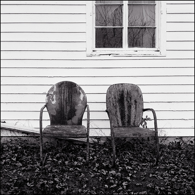 A pair of rusty metal motel chairs sit under a window outside an old white farmhouse on Sandpoint Road in Fort Wayne, Indiana. The ground is covered in fall leaves.