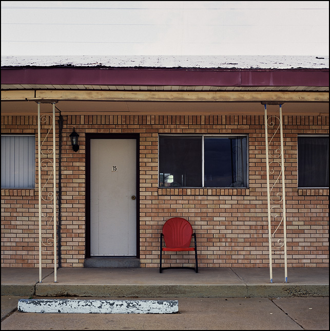 A metal motel chair sits next to the door in front of Room 15 at the San Jon Motel on Route 66 in San Jon, New Mexico.
