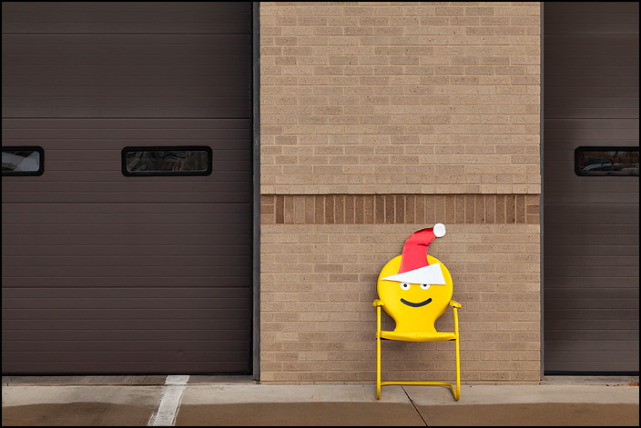 A yellow metal motel chair with an emoji face wearing a Santa hat painted on the back sits in front of Fire Station 10 at the corner of Crescent and Anthony in Fort Wayne, Indiana.