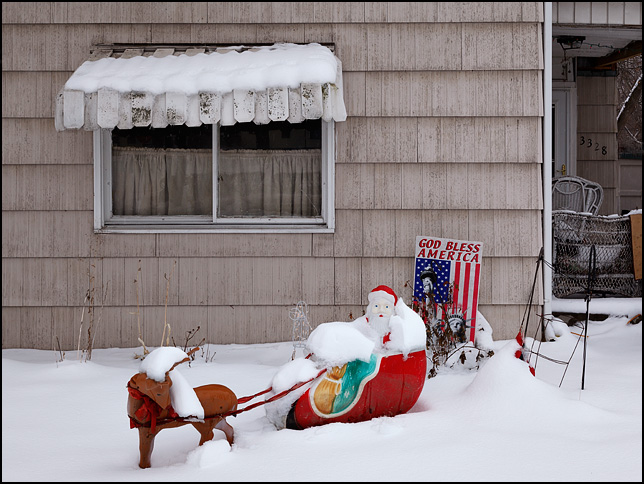 A plastic Santa Claus sits buried in snow in front of an old house with a sign that says God Bless America in the yard.