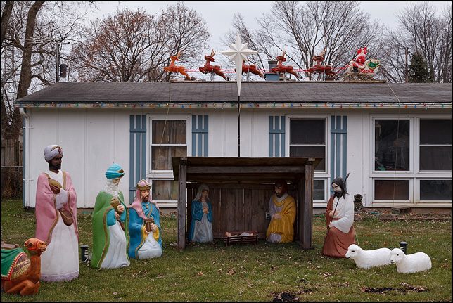 A house with a plastic Nativity Scene in the front yard and a large plastic Santa Sleigh with Reindeer on the roof on Belle Vista Boulevard in Fort Wayne, Indiana.