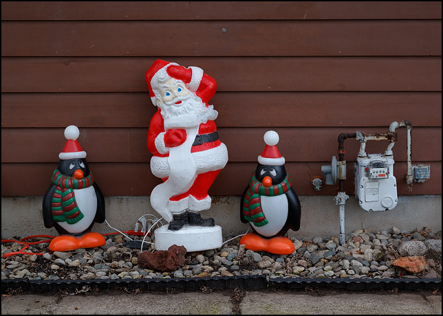A plastic Santa Claus and two plastic penguins wearing Santa hats stand in front of a house on Woodheath Avenue in Fort Wayne, Indiana.