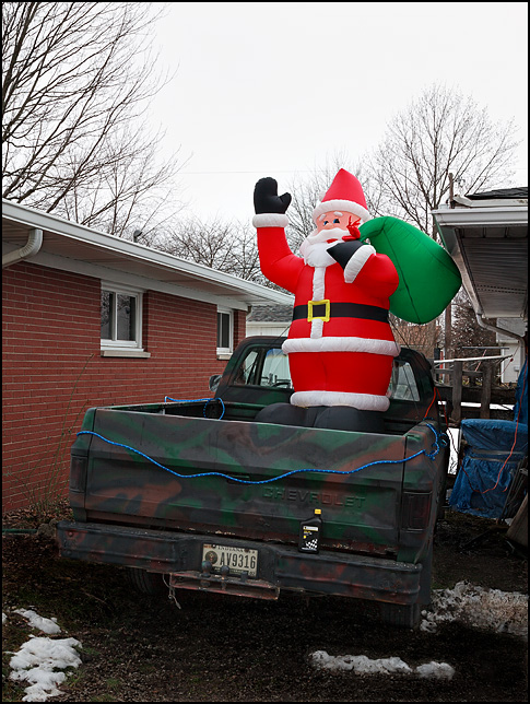 An inflatable Santa Claus standing in the bed of an old Chevrolet pickup truck that is painted in camouflage.
