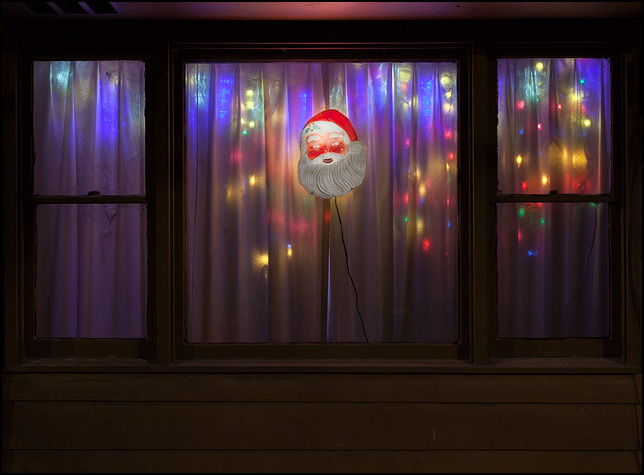A glowing lighted Santa Claus head hangs in the front window of a house surrounded by colored lights.