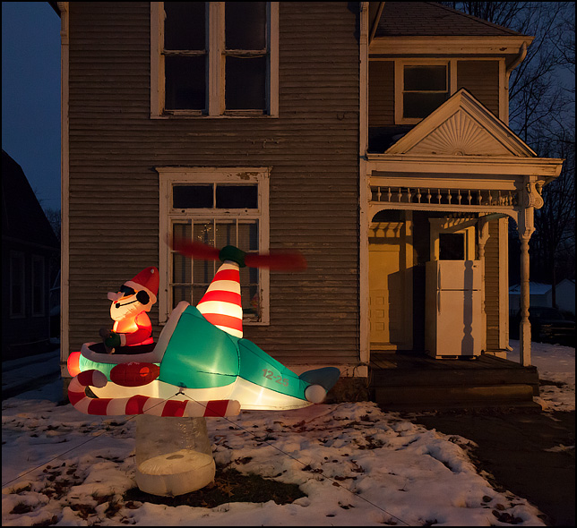 An inflatable helicopter with Santa Claus in the cockpit, photographed at night in the front yard of an old house on Broadway in Fort Wayne, Indiana. The house has a refrigerator on the front porch.