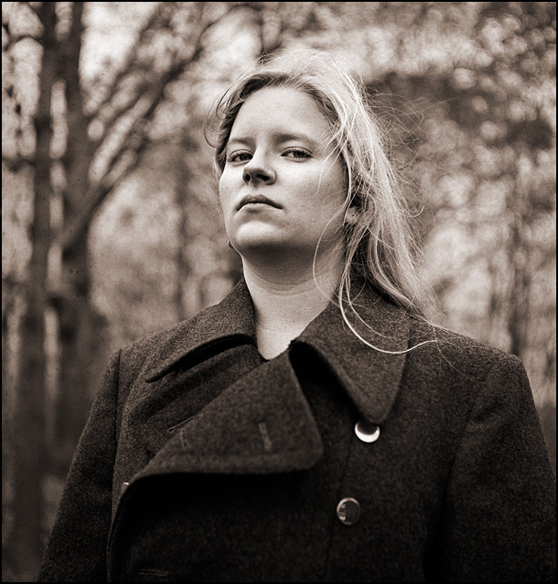 Sarah Strom wearing a Soviet Army overcoat in the forest.