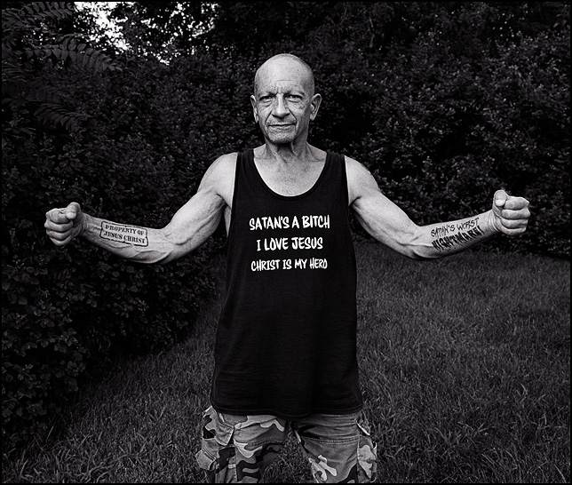 A tough-looking man wearing a tank top that says Satan is a Bitch, I love Jesus, and Christ is my Hero. He has a tattoo on one arm that says Satan's Worst Nightmare, and one on his other arm that says Property of Jesus Christ.