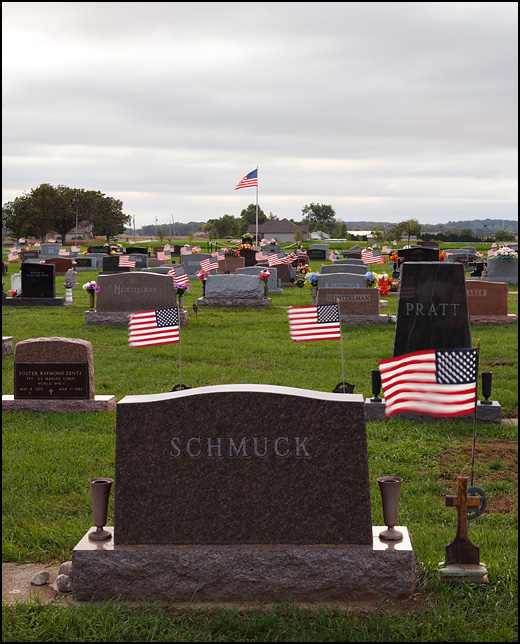 Small American flags fly from all of the tombstones at Sparta Cemetery in the small town of KImmell, Indiana. The name on the tombstone in the foreground is Schmuck.